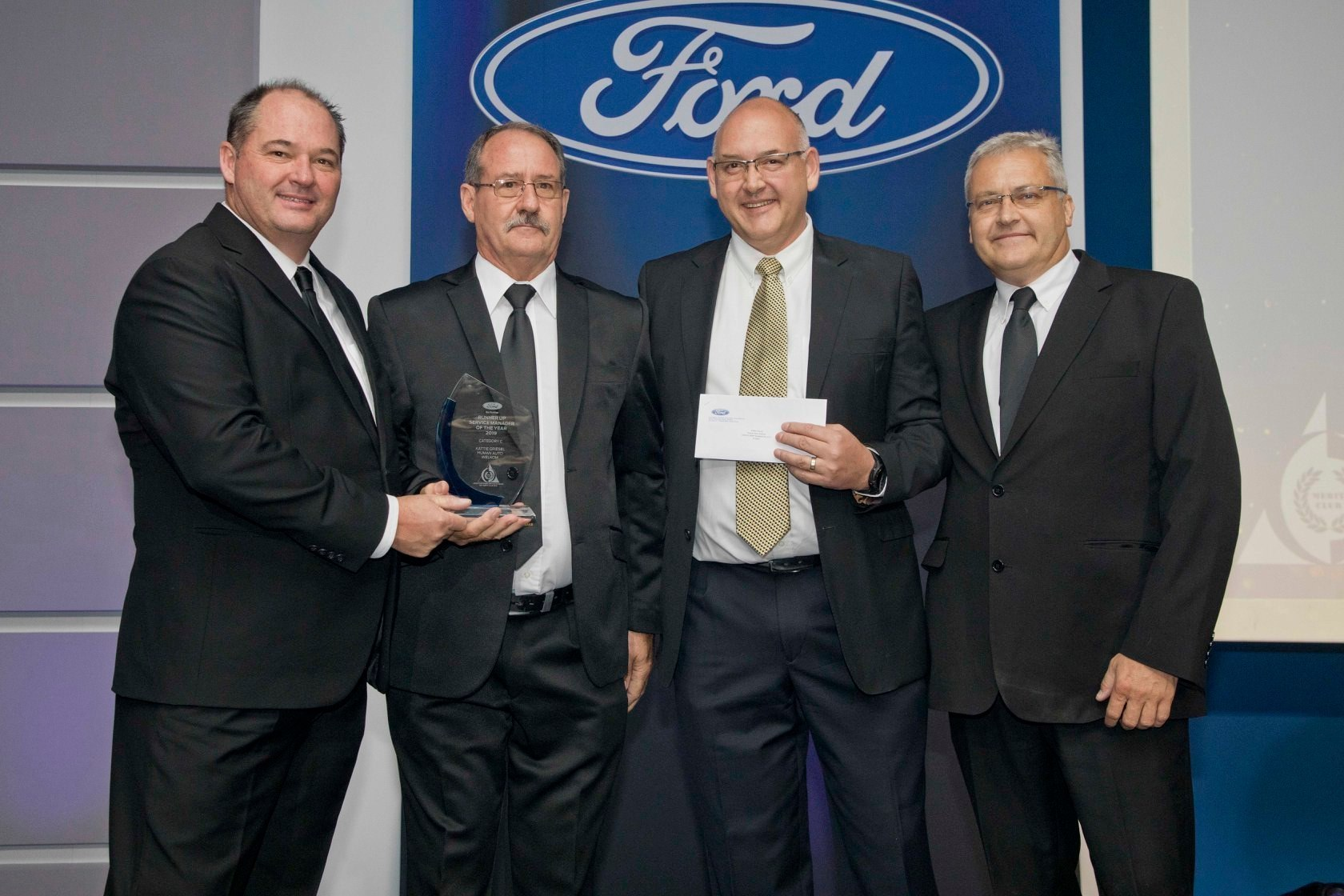 Neale Hill, CEO of Ford SA and sub-Saharan Africa, presenting the trophy to Human Auto Welkom's, Kattie Griesel. To the right is Pieter Verster (National Service Engineering Operations Manager, Ford SA) and Johnny Segaar (General Manager After Sales & Marketing, Ford SA)